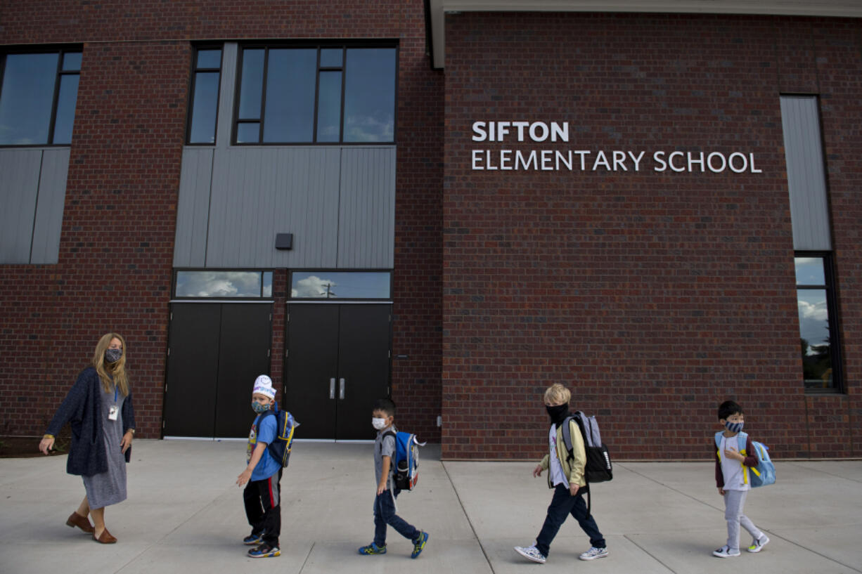 Kindergarten teacher Katie Plamondon, from left, leads students Phoenix Winmil, 5, Wes Charuchinda, 5, Emery Thomas, 6, and Jay Chou, 6, into the building for their second day of classes at Sifton Elementary School last Sept. 22. Smaller districts are exploring permanent remote options for families who choose them.