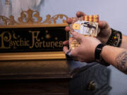 """Employee Ryan Thiessen shuffles a tarot card deck at Love Potion Magickal Perfumerie in downtown Vancouver. """"We're a spiritual place but we mix in fantasy and nerd culture,"""" said store owner Mara Fox, who reinvented her life after making it big in the band Precious Metal."""