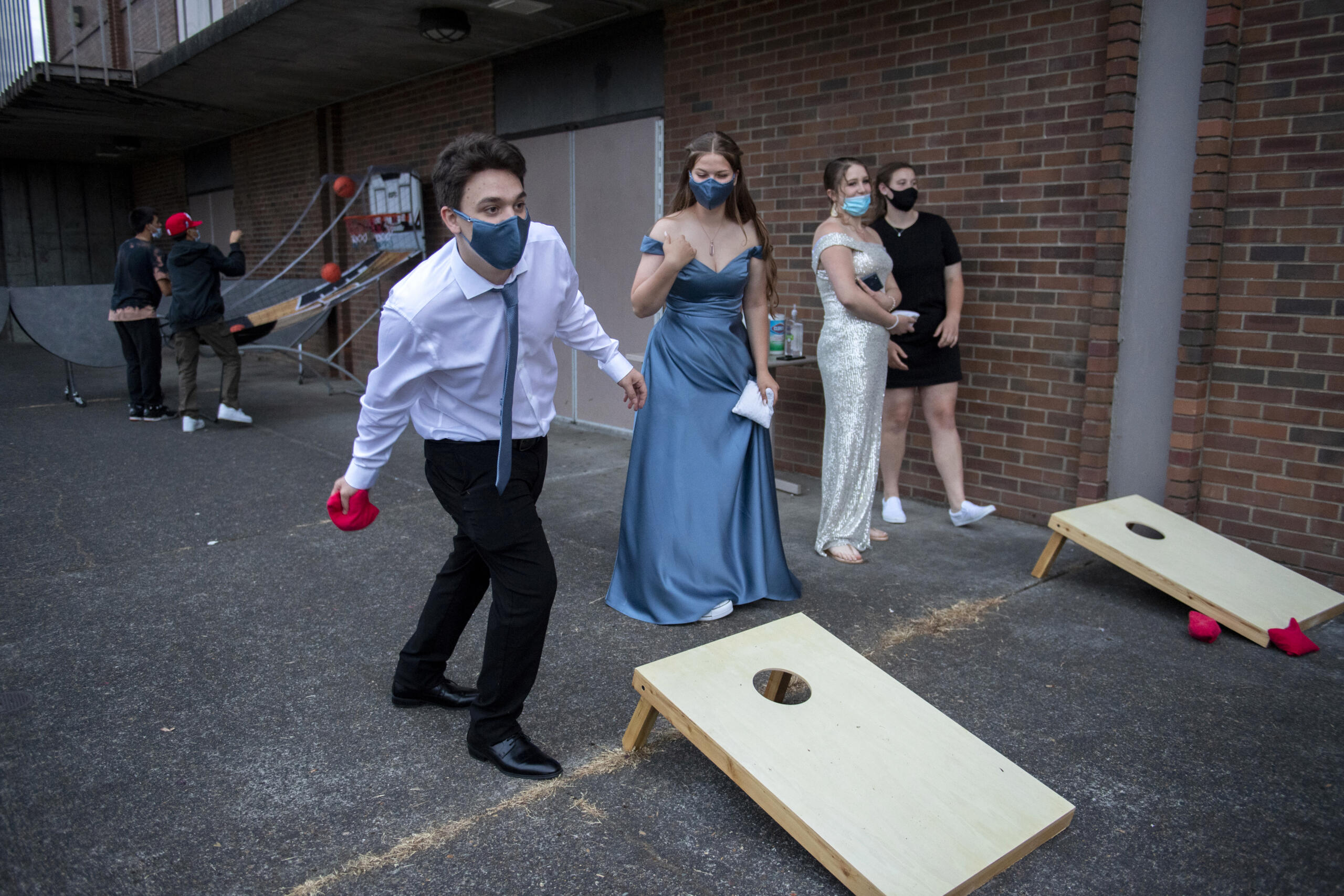 Junior Chris Boone, 18, left, takes aim while playing cornhole with fellow junior Emma Garrett, 16, outside the gym at Fort Vancouver High School on May 22. The games were part of the outdoor entertainment option for students at the unique prom, not only to offer activities as a secondary option, but also a safe outside alternative in case students didn't feel comfortable indoors as the COVID-19 pandemic continues.