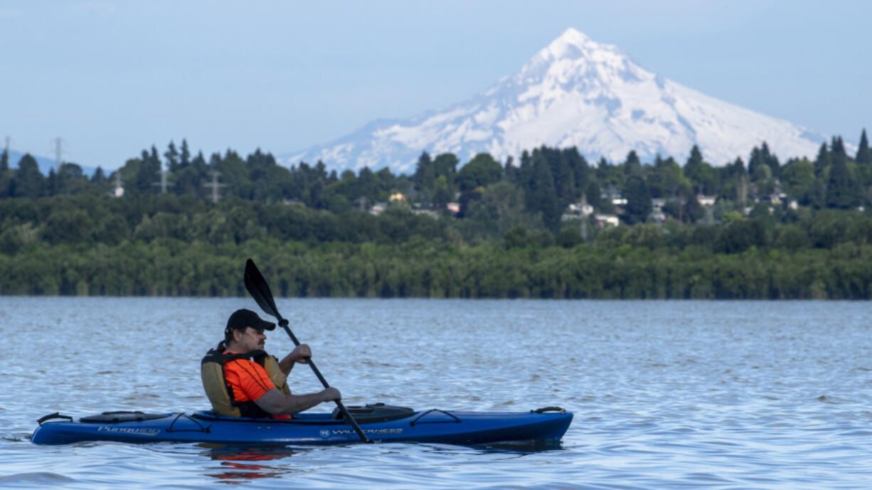 Glenn Wright paddles his kayak through the waters of Vancouver Lake, the snowy flanks of Mt. Hood in the background.