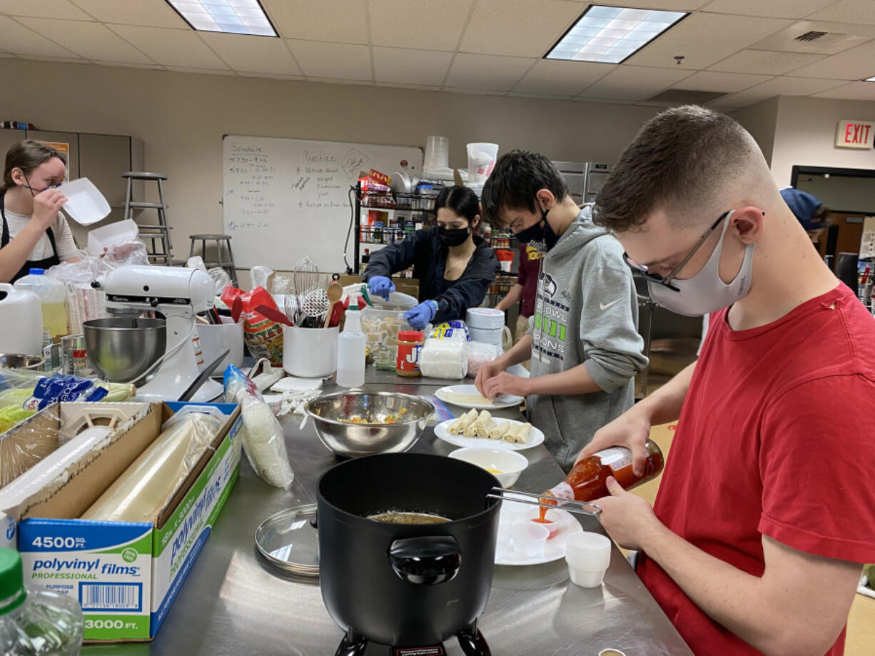 WASHOUGAL: Justus Taylor and Owen Wilkerson make food for the food fair at Washougal High School.