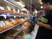 Eileen Baye, 2, left, of Vancouver and her brother, Dylan, 9, look over the selection at the Donut Nook.