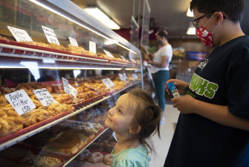 Eileen Baye, 2, left, of Vancouver and her brother, Dylan, 9, look over the selection at the Donut Nook. (Amanda Cowan/The Columbian)