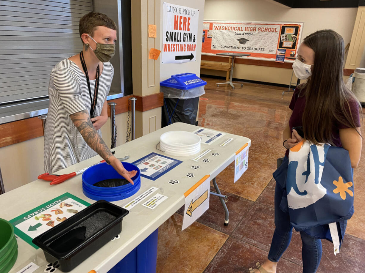 WASHOUGAL: Alex Yost and Shannon Brennan chat at a table used to sort recyclables and food waste at Washougal High School.