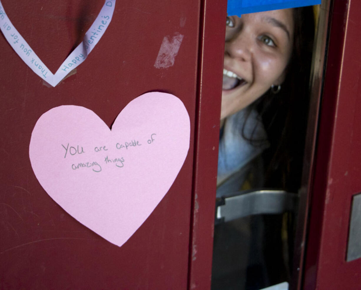 BATTLE GROUND: Prairie High School sophomore Soledad Ahumada peeks out from a door holding a heart with an inspirational message.