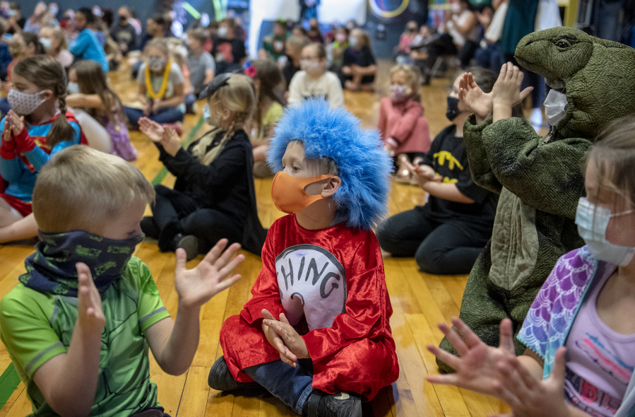 Kindergartners, dressed as their favorite superhero, join schoolmates in a round of applause for outgoing staff during an end-of-the-year assembly in the gym at Green Mountain School on Tuesday morning.