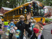 Students including first-grader Trulee Dunn, right, get a warm goodbye from teachers as they prepare to board the bus on the last day of class at Green Mountain School on Tuesday morning. It is tradition for teachers and staff to blow bubbles to bid farewell to the children but this year a bubble machine was used as well.
