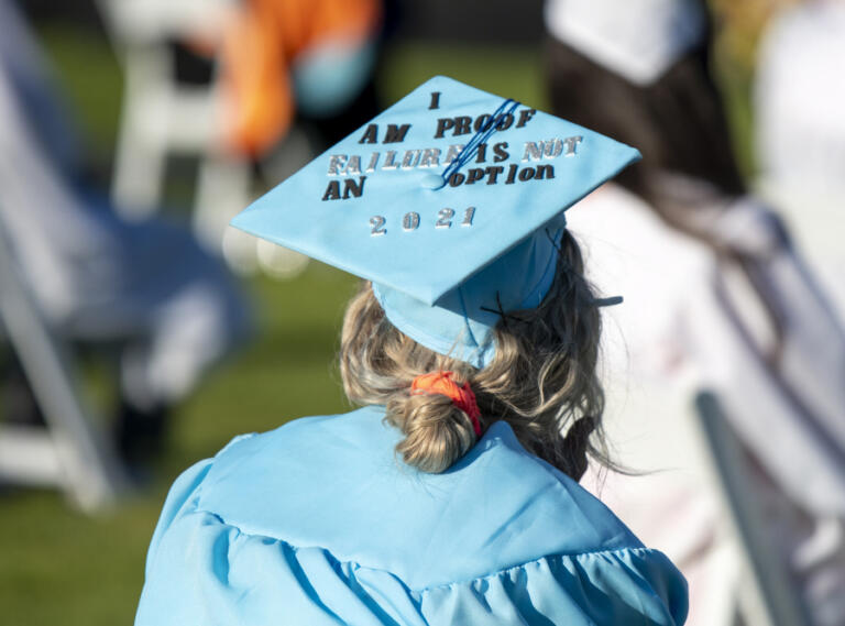 A decorated cap sits on the head of a graduate during the Clark College Commencement ceremony Thursday at Kim Christiansen Field.