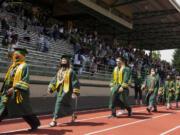 Evergreen High School graduates walk along the track during their graduation ceremony Saturday at McKenzie Stadium.