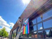 A Thirsty Sasquatch employee hangs new LGBTQ Pride banners Wednesday. Vandals tore down the old banners and smeared feces on the premises.