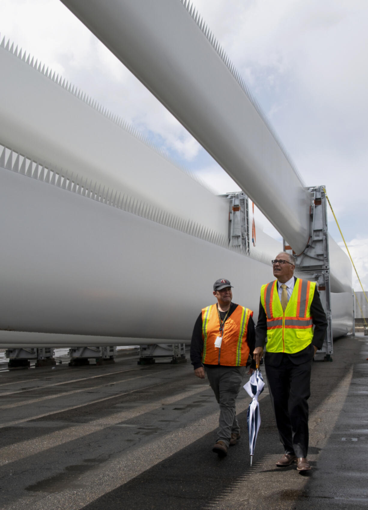 ILWU Local 4 President Cager Clabaugh walks alongside Gov. Jay Inslee as they tour a shipment of wind turbine blades at the Port of Vancouver on Tuesday.