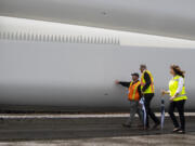 ILWU Local 4 President Cager Claybaugh talks to Gov. Jay Inslee while they walk alongside a wind turbine blade with Port of Vancouver CEO Julianna Marler on Tuesday at the Port of Vancouver. Inslee visited the Port to view an in-progress shipment of wind turbine blades that are coming through Vancouver on their way to Wasco, Ore.