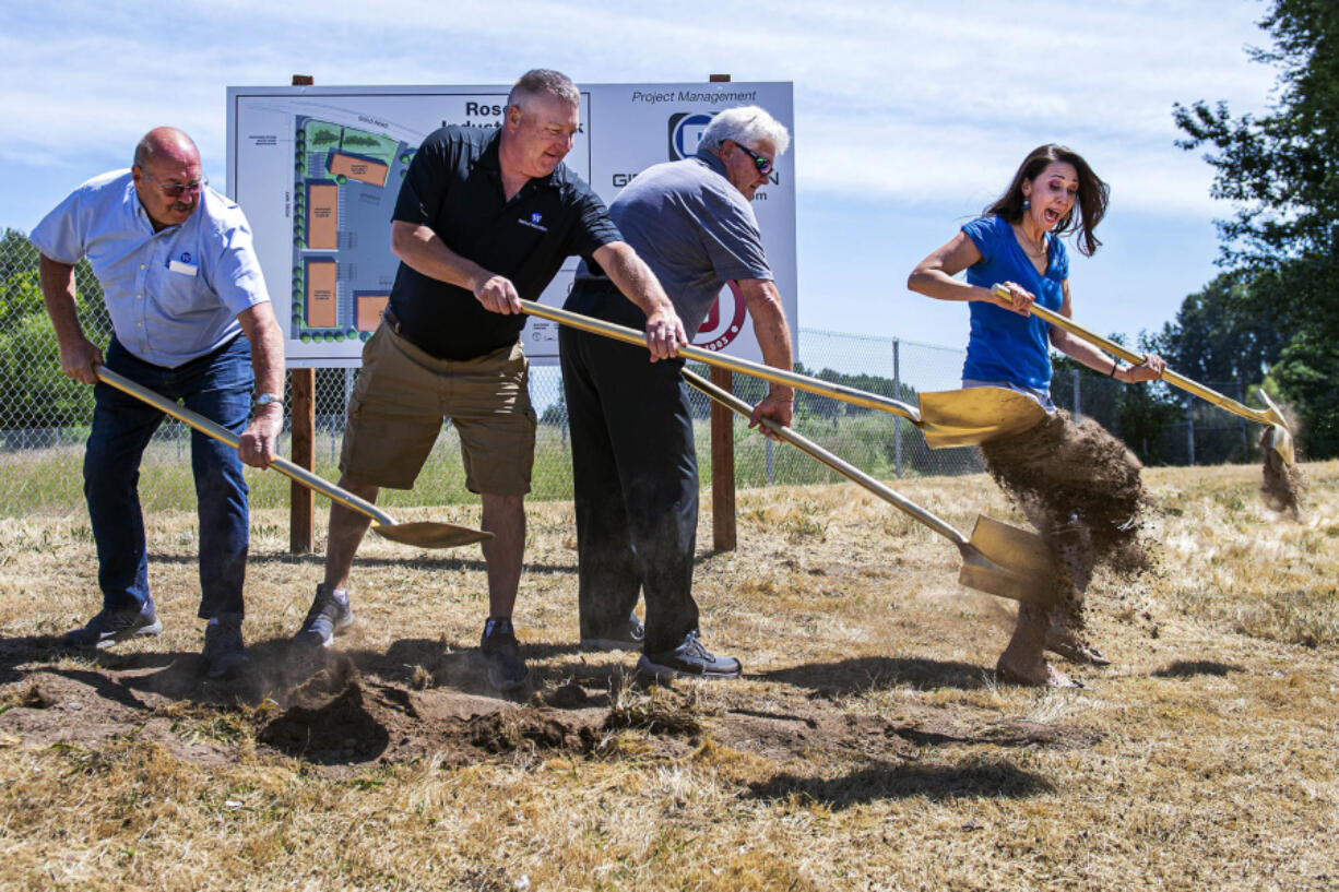 U.S. Rep. Jaime Herrera Beutler, R-Battle Ground, jumps June 4 to avoid dirt thrown by Port of Woodland Commissioner Dale Boon, left, Port of Woodland Commission President Bob Wile, second from the left, and Port of Woodland Commissioner Paul Cline.