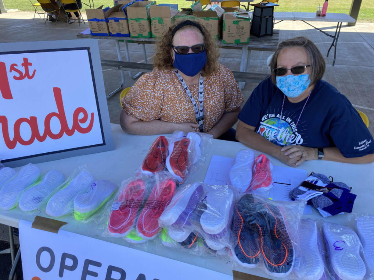 WASHOUGAL: Penny Porche and Nancy Boon, Washougal School District family resource coordinators, helped students pick up their new shoes at the Shoe-a-palooza event.