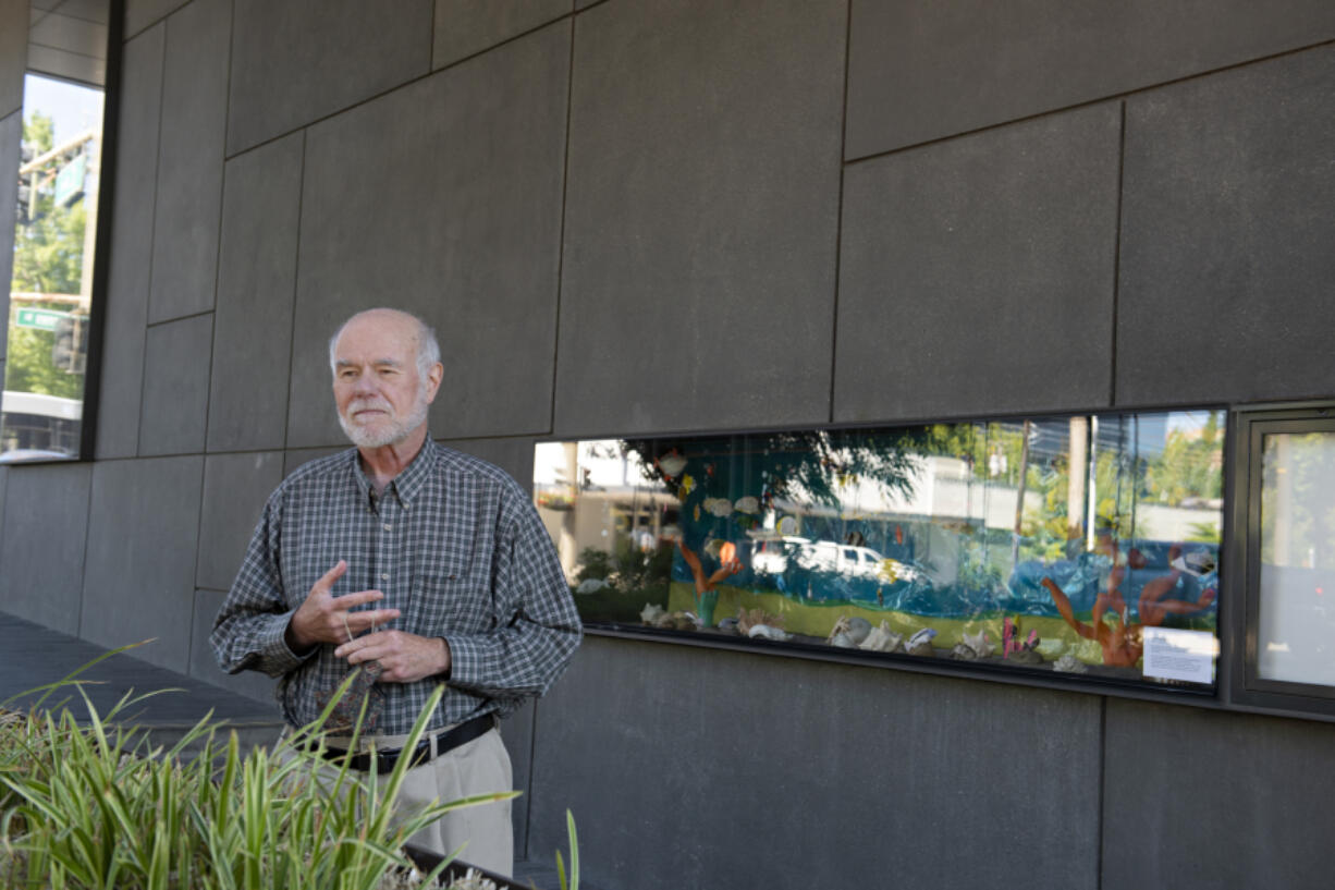 """Artist Jeff Hill shows off the """"fish tank,"""" full of his papier-mâché tropical fish, that's on display outside the Vancouver Community Library. The fish stop swimming at the end of this month, but a similar papier-mâché butterfly exhibit is on display inside the building through July."""