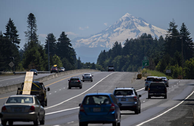 Drivers traveling east on state Highway 14 take in a scenic view as a snowcapped Mount Hood is seen in the distance under sunny skies Thursday. Forecasters expect sunny skies and summer-like temperatures for several days, with temperatures peaking near  100 degrees on Monday.