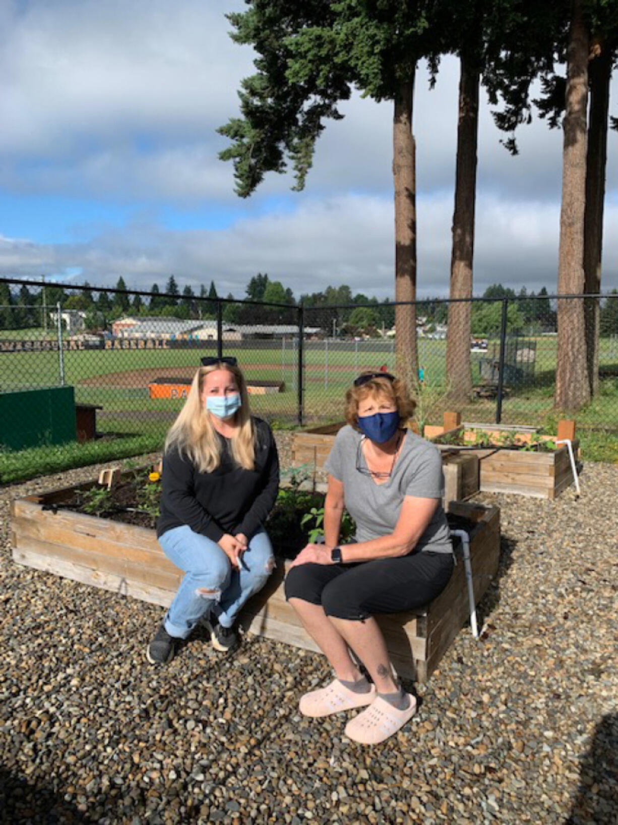 WASHOUGAL: Community member Nicole King and Washougal High School Chef Brenda Hitchins, right, take a seat on some of the school's new raised garden beds.