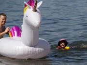 """Slava Bakhmutov holds an inflatable rainbow unicorn while Arriana, 4, swims toward it after she fell off on Saturday morning, June 26, at Cottonwood Beach in Washougal. """"She's rainbow obsessed,"""" Arianna's mother said. Temperatures climbed into triple digits on Saturday, the first of three days it is expected to do so."""