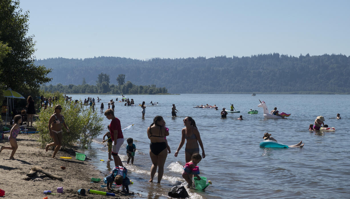People cool off in the Columbia River on Saturday, June 26, at Cottonwood Beach in Washougal. Temperatures climbed into triple digits on Saturday, the first of three days it is expected to do so.