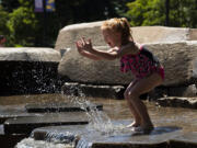Cheyanne Peters, 6, splashes water toward her mom while giggling on Friday, June 25, 2021, at the Esther Short Water Feature. Temperatures are expected to climb into the triple digits for the next three days.