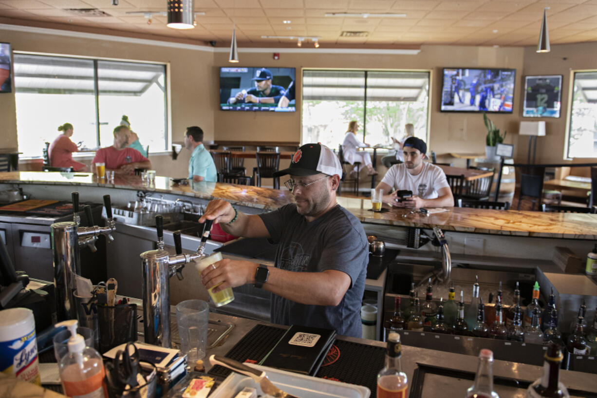Bartender Mike Dunning of Main Event Sports Grill in east Vancouver pours drinks for customers while working behind the bar on Wednesday afternoon. Statewide pandemic restrictions ended on Wednesday, allowing restaurants and bars to reopen their bar counter seating areas for the first time in more than a year.