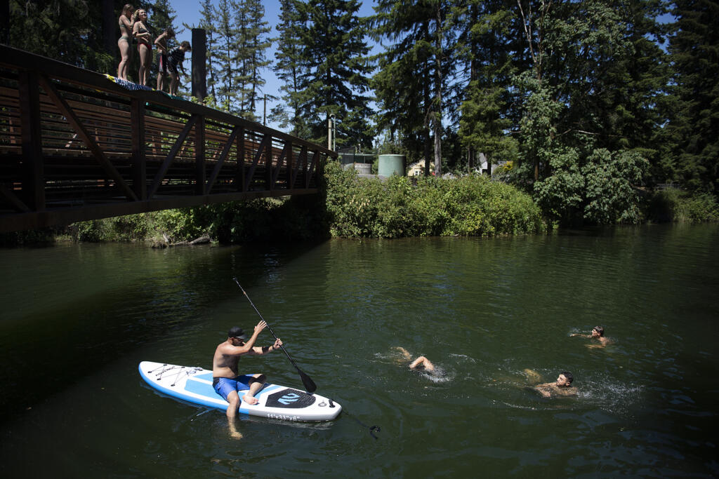 Swimmers join a stand-up paddleboarder as they gather to beat the extreme heat at Lacamas Park on Monday afternoon, June 28, 2021.