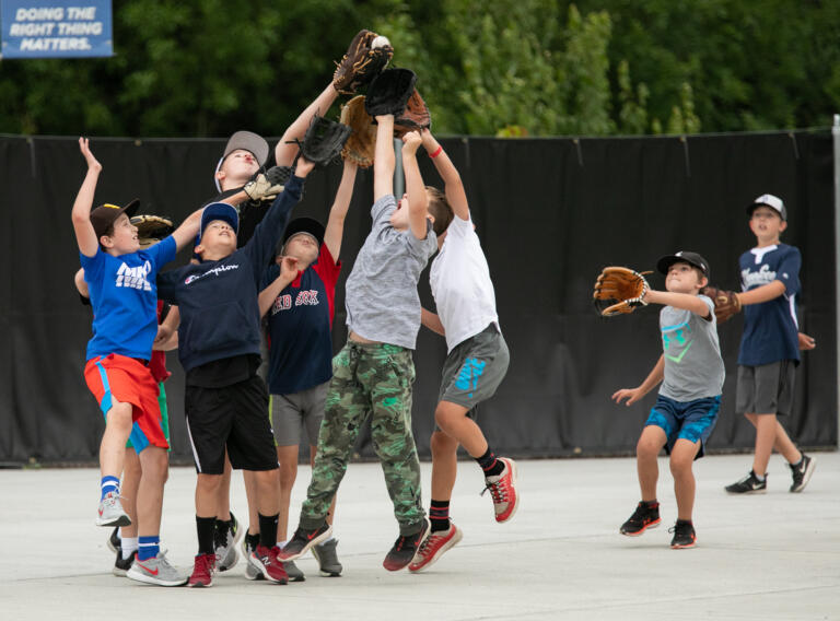 Kids play catch in the fan section as Ridgefield takes on Bellingham in a West Coast League baseball game at the Ridgefield Outdoor Recreation Complex on Wednesday, June 30, 2021.