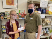 ESTHER SHORT: James Fitzgerald, executive director of nonprofit organization FISH of Vancouver, accepts a donation from 10-year-old Chloe Daarud.