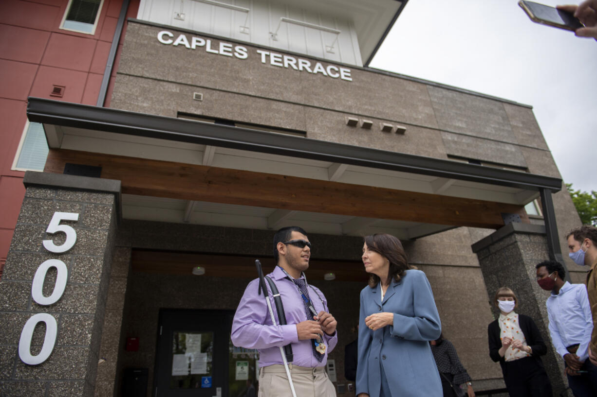 Miguel Viveros Chavez, resident at Caples Terrace, left, chats with Sen. Maria Cantwell after speaking to members of the media about the federal debate over infrastructure at Caples Terrace in Vancouver on Wednesday morning.