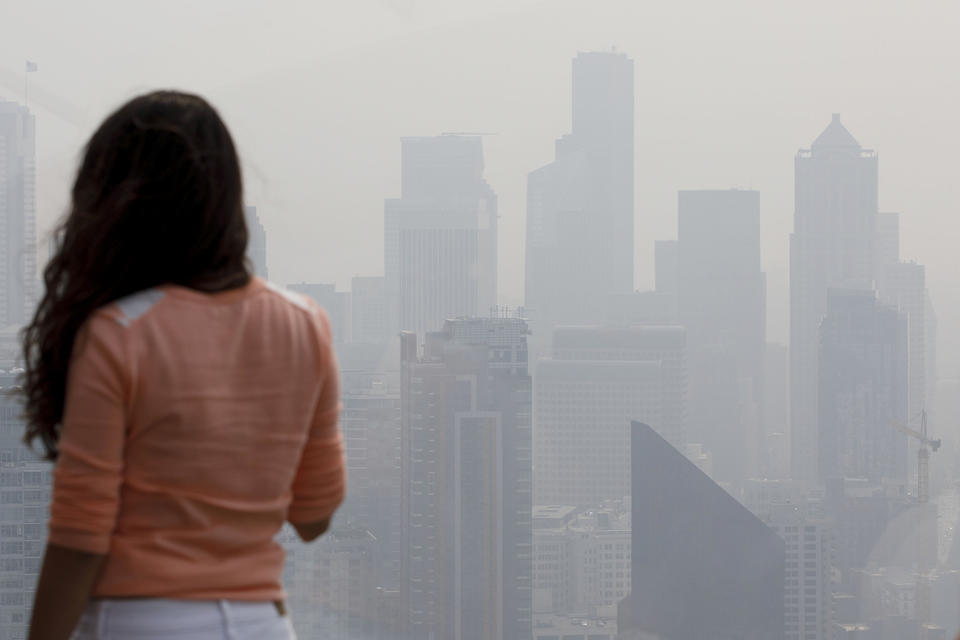A woman looks at the skyline from the Space Needle observation deck on Monday, August 20, 2018 in Seattle.