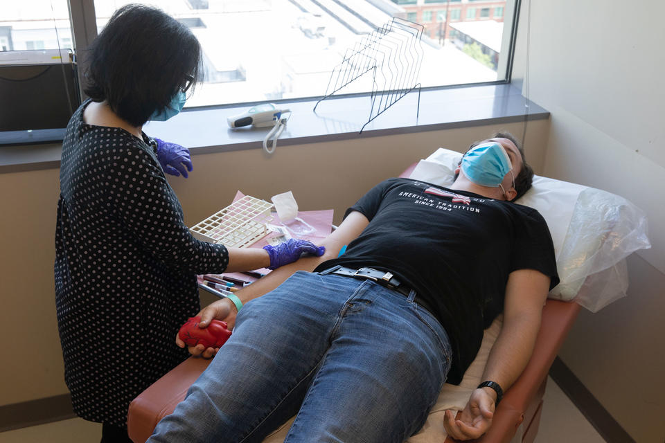 Dr. Tia Babu completes a blood draw during a patient visit with University of Washington psychology and business student Charles Jones, 21, who is participating in a Novavax COVID-19 vaccine phase 1 clinical trial for development of a second generation vaccine at the UW Virology Research Clinic in Seattle on June 10, 2021. UW researchers are partnering with Gritstone, a clinical-stage biotechnology company to produce the vaccine. (Matt M.