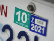 A Washington state car registration tab is shown on a vehicle in Olympia.