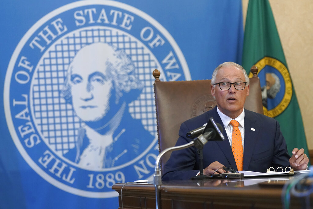 Washington Gov. Jay Inslee glances at an aide holding up an image of a visual slide being shown to viewers of a news conference, Thursday, June 3, 2021, in Olympia, Wash. Inslee announced that Washington will be the latest state to offer prizes to encourage people to get vaccinated against COVID-19. Incentives will include a series of giveaways during the month of June including lottery prizes totaling $2 million, college tuition assistance, airline tickets, and game systems. (AP Photo/Ted S.