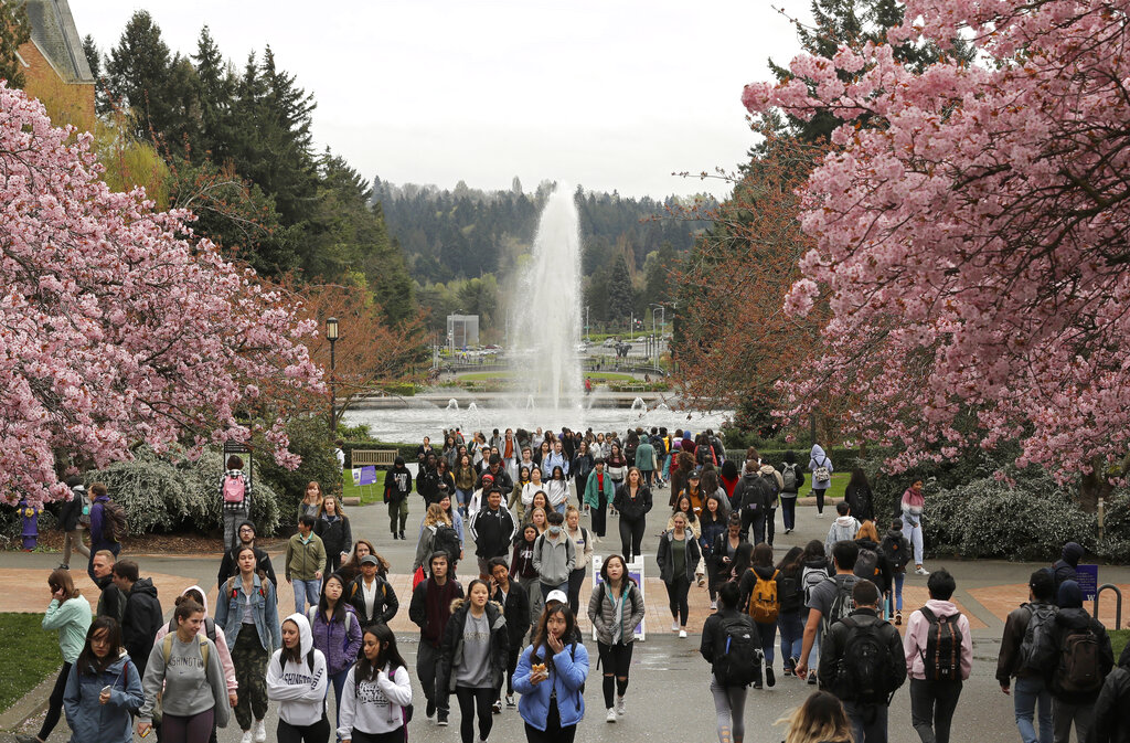 FILE - In this April 3, 2019, file photo, students walk between classes on the University of Washington campus in Seattle. Five Black police officers claiming racism at the University of Washington have filed claims for $8 million in damages. They say they were routinely insulted and demeaned by co-workers and supervisors. KOMO-TV reported Tuesday, June 22, 2021, that the officers say they were disciplined and denied promotions because of their race. (AP Photo/Ted S.