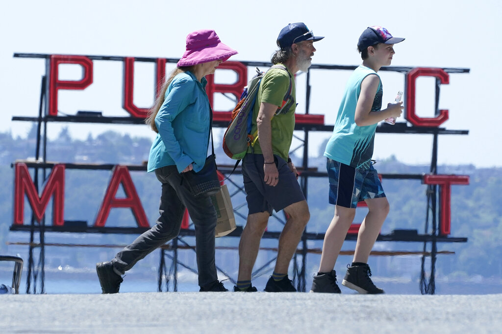 People walk near Pike Place Market, Tuesday, June 29, 2021, in Seattle. The unprecedented Northwest U.S. heat wave that slammed Seattle and Portland, Oregon, moved inland Tuesday — prompting an electrical utility in Spokane, Washington, to resume rolling blackouts amid heavy power demand.  (AP Photo/Ted S.