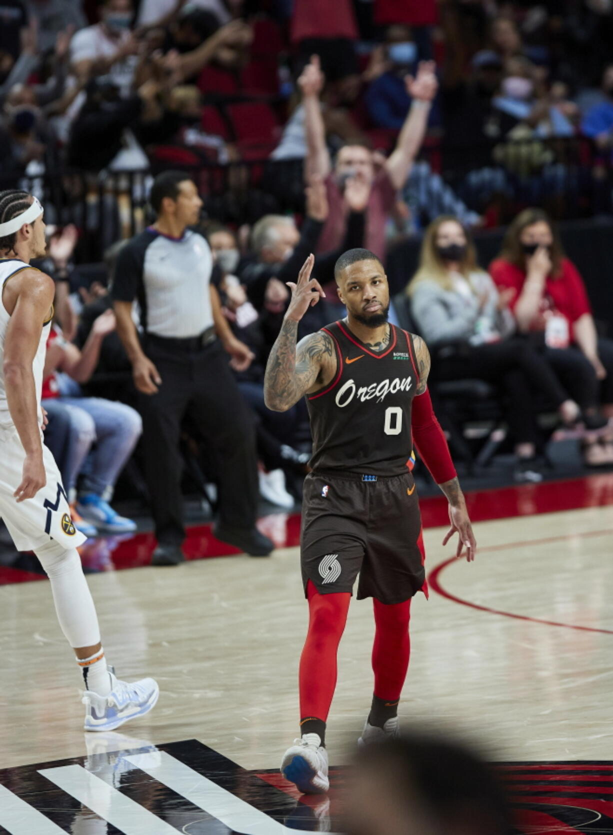 Portland Trail Blazers guard Damian Lillard reacts after making a 3-point basket against the Denver Nuggets during the first half of Game 6 of an NBA basketball first-round playoff series Thursday, June 3, 2021, in Portland, Ore.