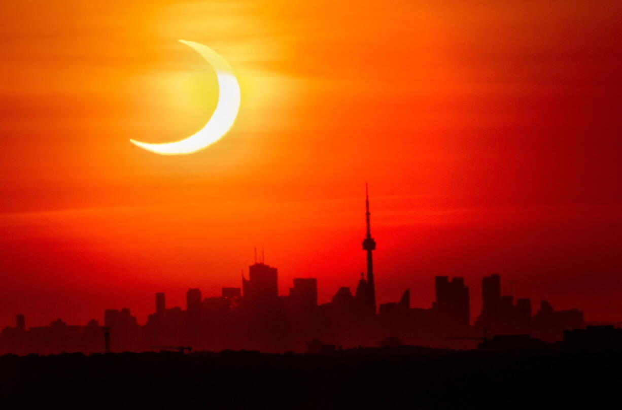 An annular solar eclipse rises over the skyline of Toronto on Thursday, June 10, 2021.