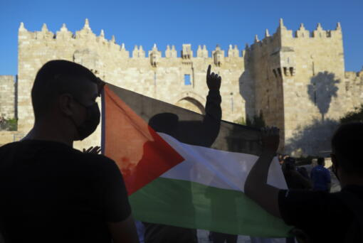 FILE - In this June 19, 2021, file photo, Palestinians demonstrators wave the Palestinian flag during protest in Damascus gate just outside Jerusalem's Old City. A new poll on U.S.