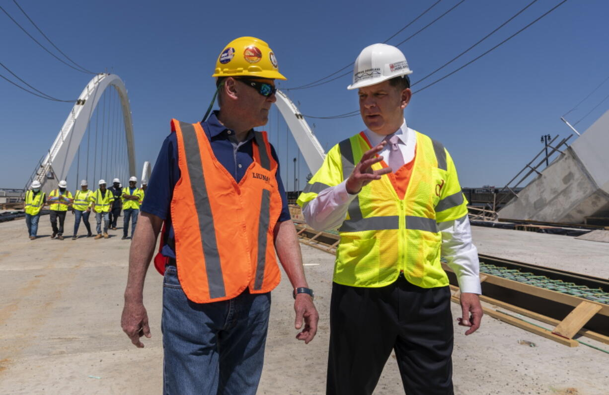 FILE - In this May 19, 2021, file photo Secretary of Labor Marty Walsh, right, visits the Frederick Douglass Memorial Bridge construction site together with District of Columbia Mayor Muriel Bowser and Secretary of Transportation Pete Buttigieg, in southeast Washington.