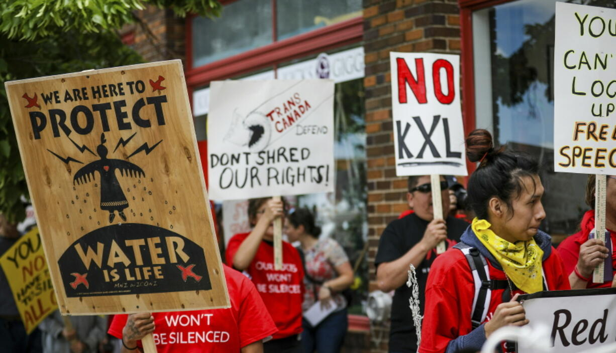 FILE - In this Jun 12, 2019, file photo, walking up Main Street the procession protesting against the Keystone XL pipeline makes its way to Andrew W. Bogue Federal Courthouse in Rapid City, S.D.