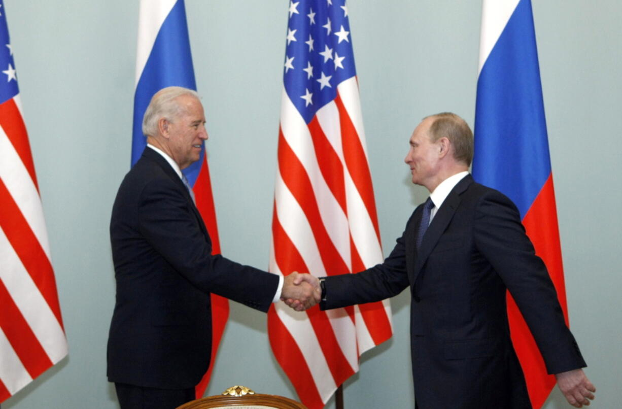FILE - In this March 10, 2011 file photo, then U.S. Vice President Joe Biden, left, shakes hands with Russian Prime Minister Vladimir Putin in Moscow.  Biden likes to say foreign policy is about building personal relationships. But unlike his three most recent White House predecessors, who all tried and failed to build a rapport with Vladimir Putin, Biden over the years in public and private comments has demonstrated that the virtue of personal diplomacy might have its limits when it comes to the Russian leader.