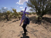 Alyssa Quintanilla, part of the Tucson Samaritans volunteer group, carries a cross May 18 to be installed at the site of the migrant who died in the desert some time ago in the desert near Three Points, Ariz. (Photos by Ross D.