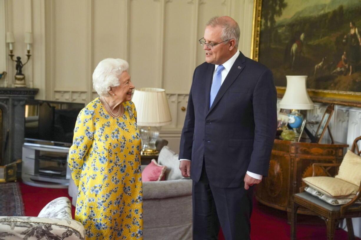 Britain's Queen Elizabeth II, left receives Australian Prime Minister Scott Morrison during an audience in the Oak Room at Windsor Castle, in Windsor, England, Tuesday June 15, 2021.