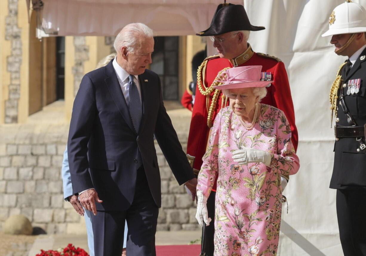 Britain's Queen Elizabeth II, right, walks with US President Joe Biden during his visit to Windsor Castle, near London, Sunday June 13, 2021.
