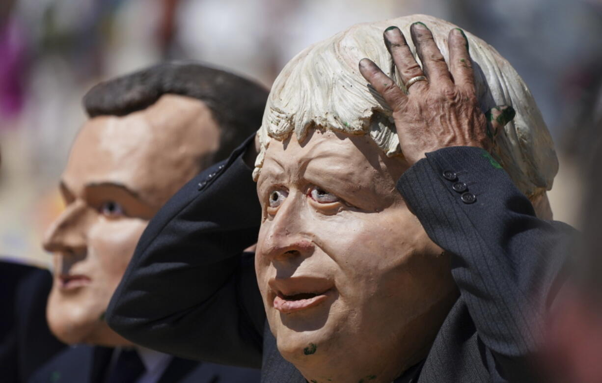 Protestors wearing giant heads portraying G7 leaders British Prime Minister Boris Johnson, right, and French President Emmanuel Macron participate in a demonstration on a beach outside the G7 meeting in St. Ives, Cornwall, England, Sunday, June 13, 2021. Leaders of the G7 wrap up three days of meetings in Carbis Bay Sunday, in which they discussed such topics as COVID-19, climate, foreign policy and the economy.