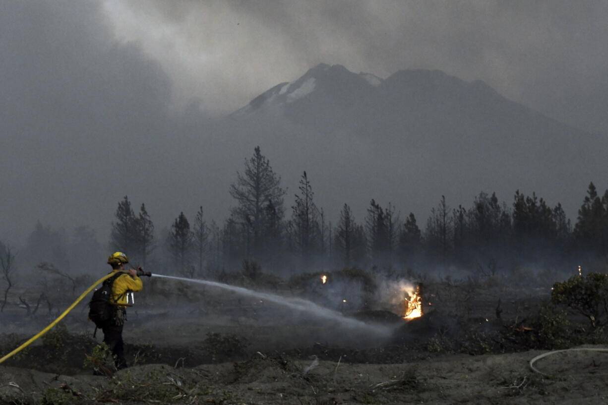 With Mount Shasta in the background, a firefighter cools down hot spots on Monday, June 28, 2021, after the Lava Fire swept through the area north of Weed, Calif.