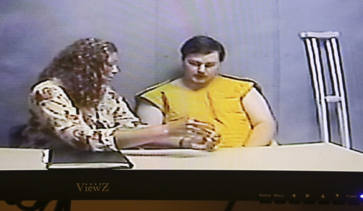 Assistant public defender Lindsay Garner, left speaks to her client Alexander Ken Jackson, 20, as he appears for his initial court appearance via video conference at the Linn County Courthouse in Cedar Rapids, Iowa, on Wednesday, June 16, 2021.  Jackson has been charged with three counts of first-degree murder, and is in custody at the Linn County Jail.