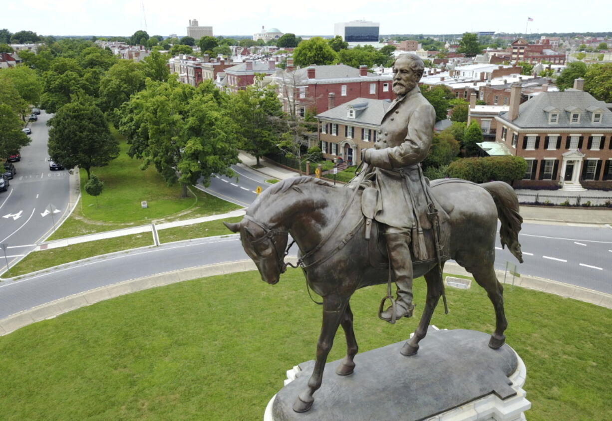 FILE - In this June 27, 2017 file photo a statue of Confederate Gen. Robert E. Lee stands in the middle of a traffic circle on Monument Avenue in Richmond, Va. If a court clears the way for the state of Virginia to take down one of the country's most prominent Confederate statues, contractors will also be removing something else from the enormous monument: a 134-year-old time capsule rumored to contain a valuable and historically significant photo of deceased President Abraham Lincoln.