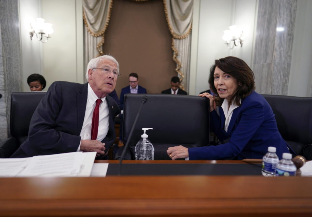Sen. Roger Wicker, R-Miss., left, and Sen. Maria Cantwell, D-Wash., chair of the Senate Commerce, Science, and Transportation Committee, prepare to hold a hearing on student athlete compensation and federal legislative proposals to enable athletes participating in collegiate sports to monetize their name, image, and likeness, at the Capitol in Washington, Wednesday, June 9, 2021. (AP Photo/J.