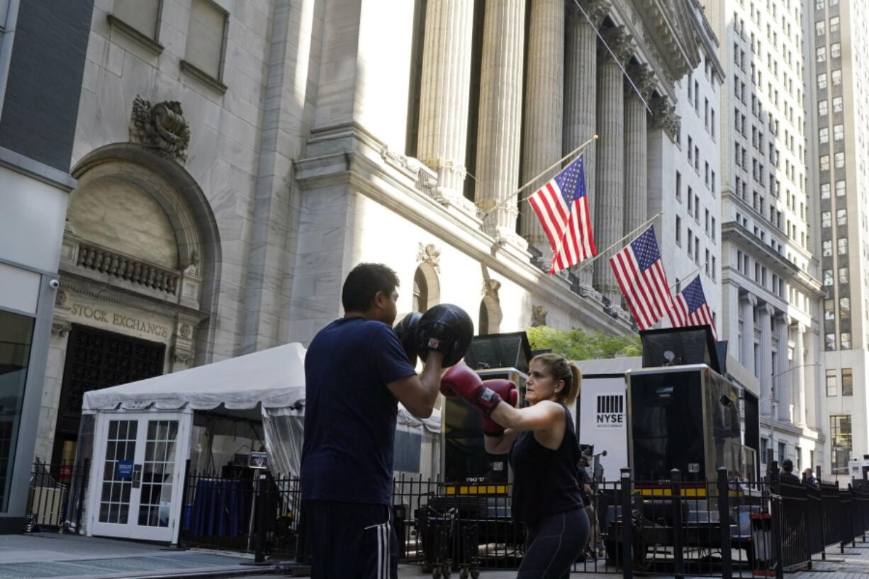 A woman and her trainer workout outside the New York Stock Exchange, Monday, June 7, 2021. Stocks are opening higher on Wall Street Thursday, June 10 nudging the S&P 500 back into the green for the week. The benchmark index was up 0.6 percent in the early going, and the tech-heavy Nasdaq was up 0.4 percent.